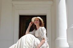 Die europäische Frau, die im Sonnenschein sitzen und der rührende Hut in der Weinlese kleiden nahe Palast an Lizenzfreie Stockbilder