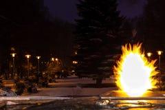 Die ewigen Flammenbrände in der Dämmerung der Nacht und im Abstand man können eine Gasse sehen, die durch Straßenlaternen belicht stockbild
