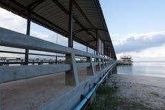 Die Fähre ist am langen Pier gegen den blauen Himmel Stockfoto