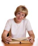 Die fällige Frau mit Buch hinter einer Tabelle Lizenzfreie Stockfotos