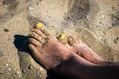 Die Füße der Frau auf einem Meersand auf dem Strand stockbilder