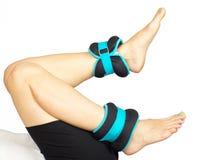Die Füße der Frau, die mit den Knöchelgewichten, lokalisiert trainieren stockbild