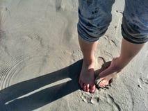 Die Füße der Kinder, die im Sand am Strand spielen Stockfotografie