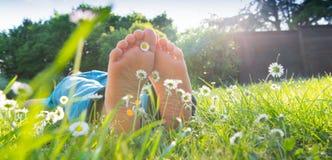 Die Füße der Kinder im Gras Stockfotografie