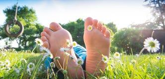 Die Füße der Kinder im Gras Lizenzfreie Stockbilder