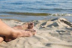Die Füße der Mannlüge auf Sand Lizenzfreies Stockfoto