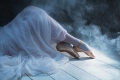 Die Füße der sitzenden Ballerina im Rauche Stockfotografie