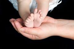 Die Füße des Babys in der Hand des Elternteils lizenzfreie stockfotografie