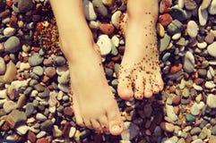 Die Füße des Kindes auf einem Strand im kleinen Farbkiesel an einem sonnigen Tag des Sommers Lizenzfreie Stockbilder