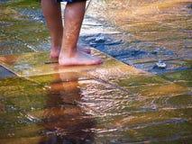 Die Füße des Kindes an einem Wasser-Spielplatz oder einer Pfütze Lizenzfreies Stockfoto
