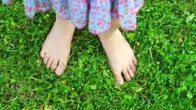 Die Füße des Mädchens auf dem grünen Gras Stockfotos