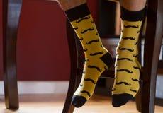 Die Füße des Mannes mit fantastischen Socken druckten mit den Schnurrbärten Lizenzfreie Stockfotos