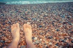 Die Füße eines jungen Mannes, der auf dem Strand sitzt Stockfotos