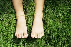 Die Füße eines kleinen Jungen auf Wiese lizenzfreie stockfotos