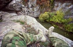 Die Füße eines Mannes auf der Bank von einem Gebirgsfluss Stockfotografie