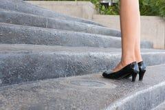 Die Füße und Bein der Geschäftsfrau schwarzen hohen Absatz tragend beschuht goin Stockfotos