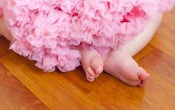 Die Füße und der rosa flaumige Rock des Babys Stockfotos