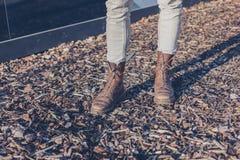 Die Füße und die Beine von tragenden Stiefeln einer Person Stockfotos