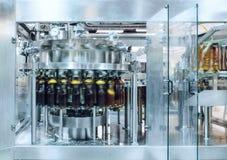 Die Füllmaschine gießt Bier in Plastik-HAUSTIER-Flaschen Lizenzfreies Stockfoto