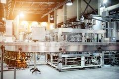 Die Füllmaschine gießt Bier in Plastik-HAUSTIER-Flaschen Lizenzfreie Stockfotografie