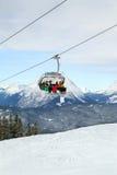 Die fünf Skifahrer sind durch Sesselbahn steigend Lizenzfreies Stockfoto