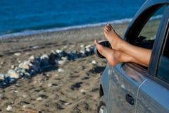 Die Fahrwerkbeine der Frau, die heraus ein Autofenster baumeln stockfotografie