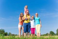 Die Familie, die auf Wiese steht - bringen Sie mit Kindern hervor Stockbild