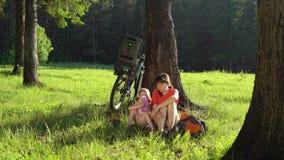 Die Familie liegt bei den Fahrrädern im Sommerwald an einem sonnigen Tag stock footage