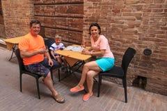 Die Familie sitzt an einem Cafétisch in der schmalen Straße von Italien Lizenzfreie Stockbilder