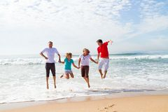 Die Familie springend auf Strand Lizenzfreie Stockfotografie