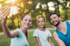 Die Familie steht im Park still, nachdem sie Sport gespielt hat Eine Frau macht selfie mit ihrer Familie Lizenzfreies Stockbild