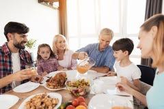 Die Familie trat am festlichen Tisch für Danksagung zusammen Der alte Mann verschüttet ein Glas Saft Lizenzfreie Stockbilder
