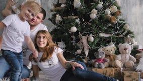 Die Familie trat um den Weihnachtsbaum zusammen Weihnachtsinnenraum stock video