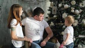 Die Familie trat um den Weihnachtsbaum zusammen Weihnachtsinnenraum stock video footage