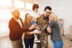 Die Familie trifft einen Mann in der Tarnung zu Hause lizenzfreie stockfotos