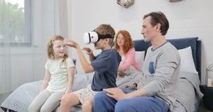 Die Familie, welche die Sohn-Spiel-Spiele tragen Gläser der virtuellen Realität im Schlafzimmer betrachten, die Eltern und die Ki stock video footage