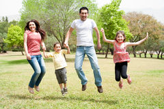 Die Familie zusammen springend in den Park Stockbild