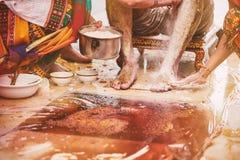 Die Familienmitglieder, die das Gelbwurzpulver haldi kleben, ölen Misch mit Milch auf Bräutigam ` s Füßen und Körper stockfotos