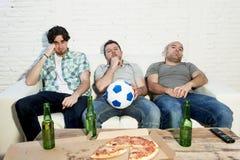 Die fanatischen Fußballfane der Freunde, die fernsehen, passen mit Bierflasche- und Pizzaleidendruck zusammen Stockbild