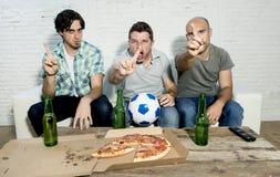 Die fanatischen Fußballfane der Freunde, die fernsehen, passen mit Bierflasche- und Pizzaleidendruck zusammen Stockbilder