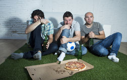 Die fanatischen Fußballfane der Freunde, die fernsehen, passen mit Bierflasche- und Pizzaleidendruck zusammen Lizenzfreies Stockbild