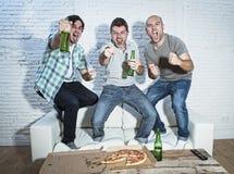 Die fanatischen Fußballfane der Freunde, die Spiel im feierndem Fernsehen aufpassen, gehen lizenzfreie stockfotografie