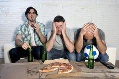 Die fanatischen Fußballfane der traurigen frustrierten Freunde, die fernsehen, passen mit dem entmutigten Bier zusammen Lizenzfreies Stockbild