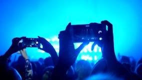 Die Fans, die ihre Hände wellenartig bewegen und halten das Telefon mit Digitalanzeigen stock video footage