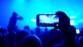 Die Fans, die ihre Hände wellenartig bewegen und halten das Telefon mit Digitalanzeigen stock footage