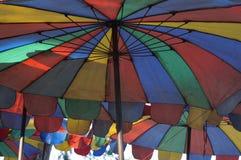 Die Farben des Strandschirms sind Symbole des Sommers Stockfotografie
