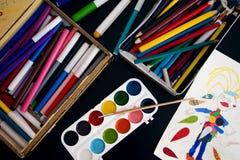 Die Farben, die Bleistifte, die Markierungen und die Zeichnung der Kinder auf der schwarzen Tabelle Lizenzfreie Stockfotos