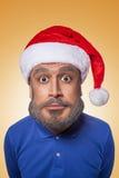 Die farbige Karikatur des lustigen Weihnachtsmanns mit Großkopf und blauem Hemd, roter Hut mit grauem Bart, überraschtes Schauen Lizenzfreies Stockbild