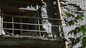 Die Fassade des alten zerstörten Backsteinbaus mit zerbrochenen Fensterscheiben im Industriegebiet der Stadt Die Demolierung von stock video footage