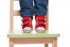 Die Füße des Kindes, die auf dem kleinen Stuhl auf Tiptoe stehen Lizenzfreies Stockfoto